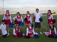 Cheerleaders pose together outside