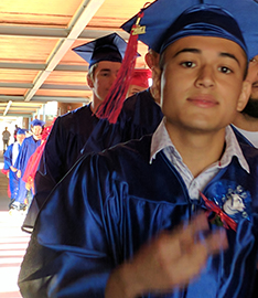 Graduate poses as he holds up a peace sign