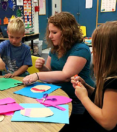 Teacher helps students with a project