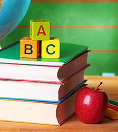 stack of school books with blocks and apple