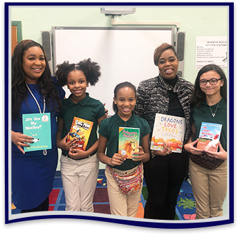 East Orange staff member with four happy students holding up books