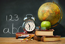 An apple, clock, globe, books, glasses and pencils in front of a blackboard