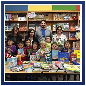 Students and teachers pose with books in a library