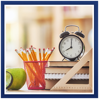 A clock, ruler, pencils, books, apple and magnifying glass