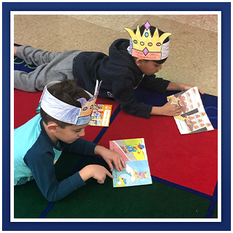 students reading on floor with paper crowns
