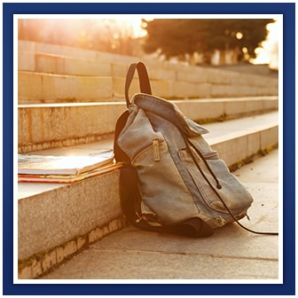 Backpack and notebooks sit on outdoor steps