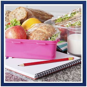 Lunchbox with food inside, a glass of milk and a notebook with a pencil on top of it