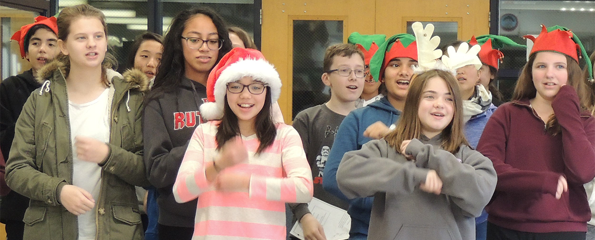 Students dressed as Christmas characters dance together