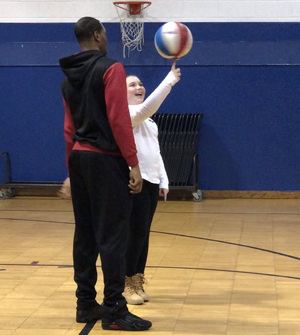 Basketball player standing with a student balancing a spinning ball on their finger