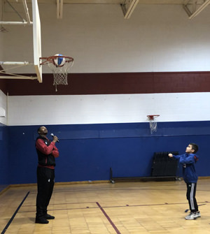 Basketball player watching student throw basketball through hoop