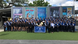 The Paramus High School Spartan marching band pose in front of posters