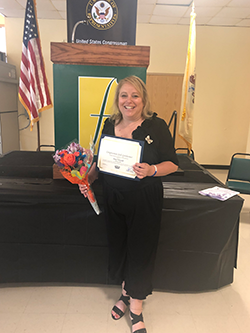Dana Folcarelli poses with a certificate and flowers