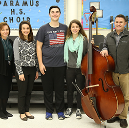 Students and teachers pose together with a large instrument