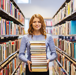 Woman holds stack of books in a library