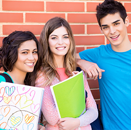 Students pose together in front of a brick wall
