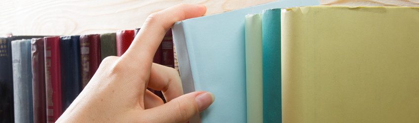 Hand grabs book from a shelf