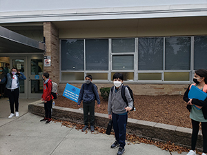 Students in masks posing for photo while entering school