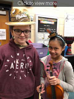 Click to view more. Two students pose with musical accessories.