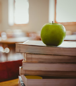 Apple sits on a stack of books in a classroom
