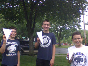 Three students holding paper airplanes