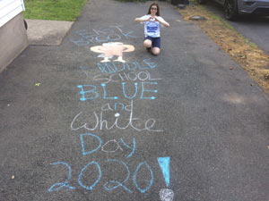 Student standing by her chalk artwork for Blue and White Day 2020