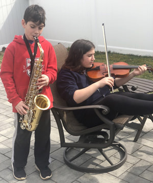 Two students playing instruments at home