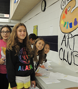 Four female students pose together next to an art club sign