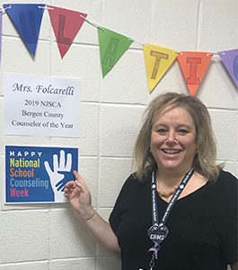 Mrs. Folcarelli poses with a 2019 NJSCA Bergen County Counselor of the Year poster in her honor