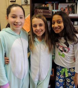 Three female students wearing pajamas pose together