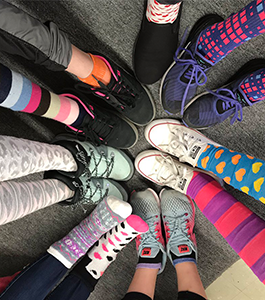 Students wearing patterned socks form their legs and feet in a circle