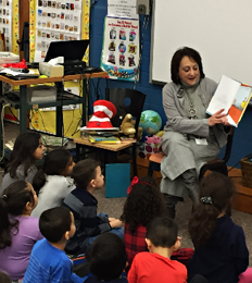 Teacher reads a book to students