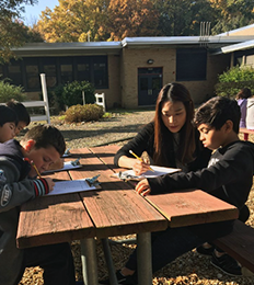 Teacher working with students outside at a picnic table