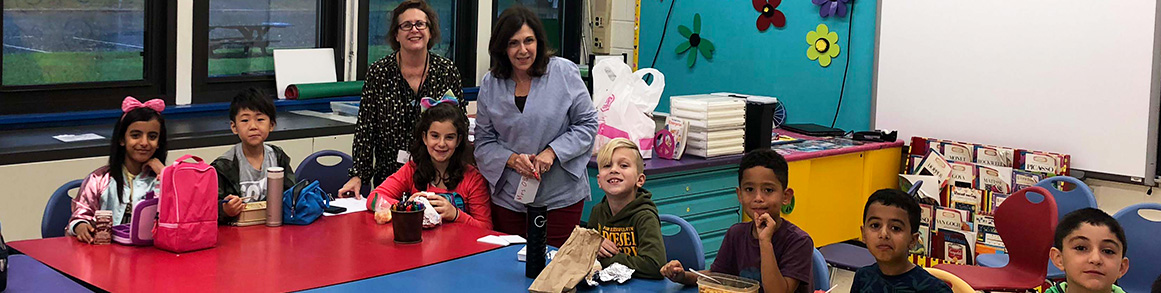 Principal O'Boyle posing for a picture with elementary students eating lunch in the classroom