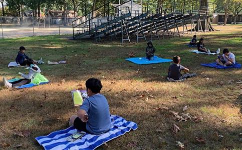 Mrs. Schafer's third grade class reading outside