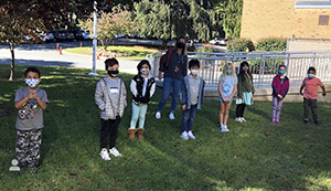 Group students enjoying some outside time wearing face masks