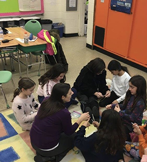 Students and teacher sit in a circle on the rug learning crochet