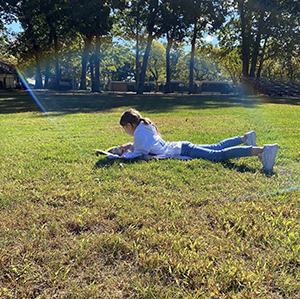 Student reading outside on the grass