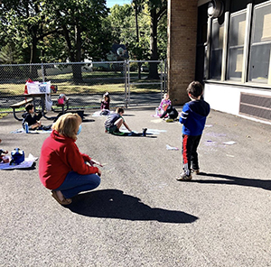 Teacher with her students enjoying the outside space on campus