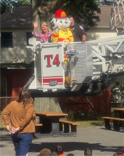 Teacher with Dalmation Firefighter mascot in crane