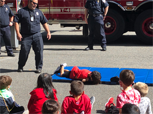 Student laying on mat for safety demonstration