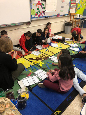 Mrs. Mandara teaching students while seated on the floor