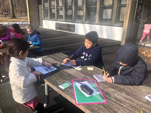 Students reading books outside at a picnic table