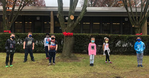 Students standing around trees with red ribbons