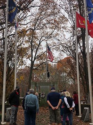 Group of veterans standing in front of memorial
