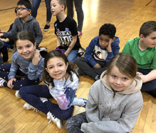 Students pose together on a gym floor