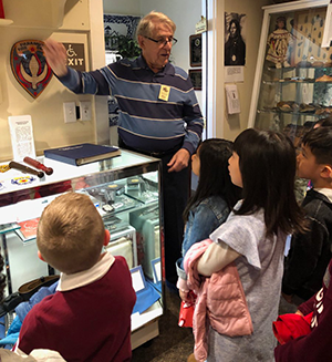 Students participate in the Behnke Museum tour as an adult speaks to them