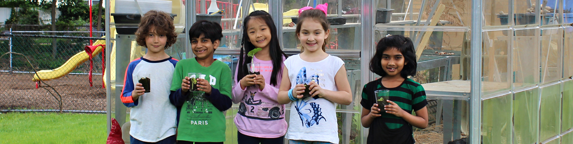 Five students pose outside of a greenhouse holding plants in soil in plastic cups