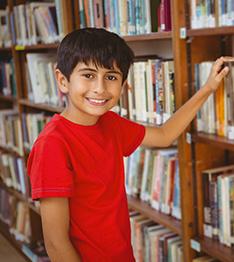 Student poses next to a bookshelf