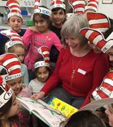 Students dressed up as the cat in the hat surround a teacher reading Dr. Seuss