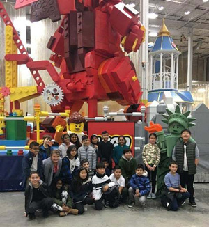Students standing in front of a Lego float